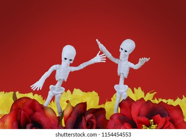A pair of skeleton party favors appear to be celebrating among silk red roses and yellow paper marigolds on a red background. Great image for Mexican Day of the Dead October holiday . Vignette added.