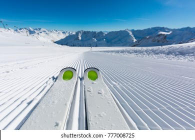 Pair of ski tips standing on the fresh snow on newly groomed  ski slope at ski resort on a sunny winter day.