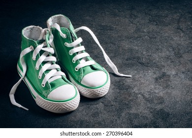 Pair of small green shoes from above on dark background with blank space
