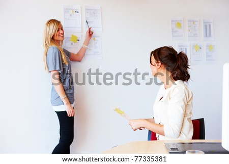 A pair of smiling businesswomen are discussing plans that have been attached to an office wall. Horizontal shot.