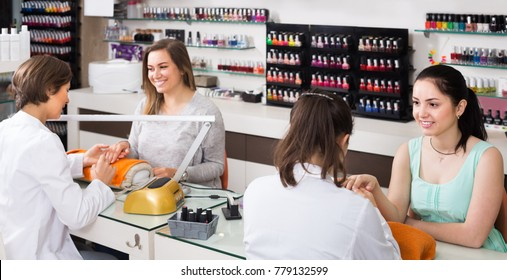 pair of smiling women clients getting manicure in modern nail salon