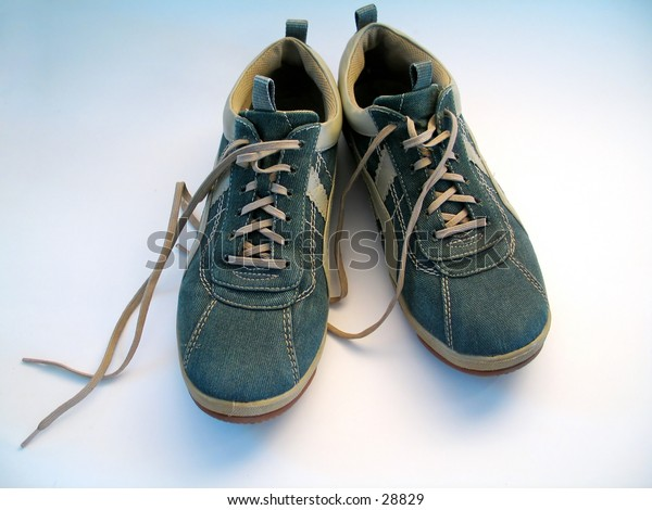 A pair of sneakers. Focus on both sneakers. Shoelaces untied.
