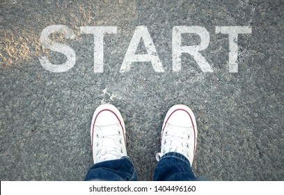 Pair of sneakers on  asphalt road with yellow print of the word start for the concept of starting point.  Step into the future