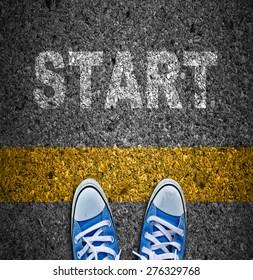Pair of sneakers on road with yellow print of word start for the concept of starting point.