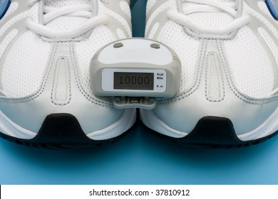 A pair of sneakers and a pedometer on a blue background, walking for a healthy heart