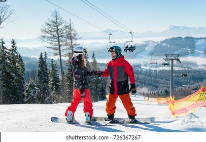 Pair of snowboarders on top of a ski slope at winter resort downhill on a sunny day. Man holds a woman's hand against the backdrop of a ski-lift and snow-capped mountains. Bukovel