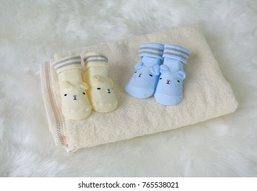 A pair of socks for newborns on a white wool background.