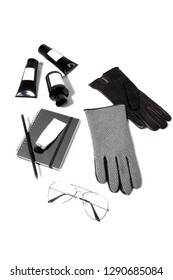 Pair of soft leather grey and lack gloves, hand cream, black bottle of perfum, aviator glasses in gold and grey craft sketchpad isolated on white