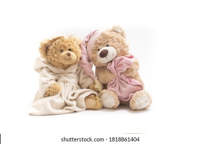 A pair of soft toy bears on a white background. Sleepy bear in a cap with a blanket and a bear in a dress. Concept of friendship, childhood, relationships, sleep, falling asleep, dreams. Horizontal.