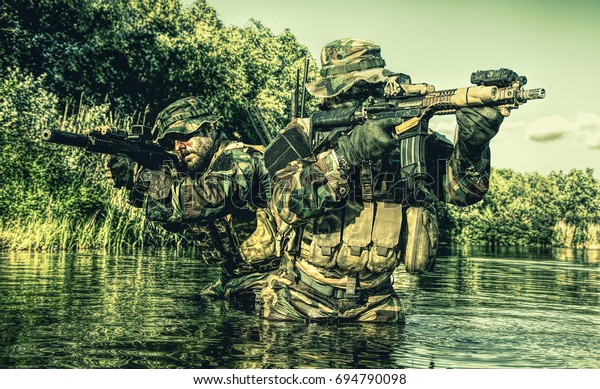 Pair of soldiers in action during river raid in the jungle waist deep in the water and mud and covering each other