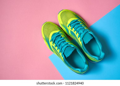 Pair of sport shoes on colorful background. New sneakers on pink and blue pastel background, copy space. Overhead shot of running shoes. Top view, flat lay