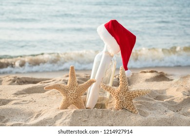 Pair of starfish with Santa hat on message in a bottle in beach sand