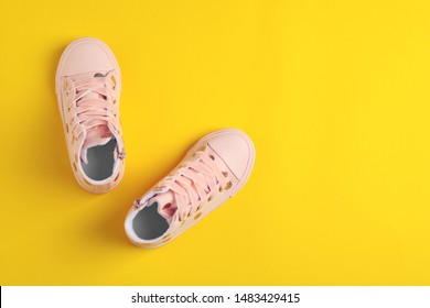 Pair of stylish child shoes on yellow background, flat lay. Space for text