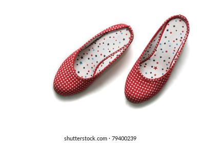 A pair of stylish flat shoes, with polka dotted pattern, isolated on white background.