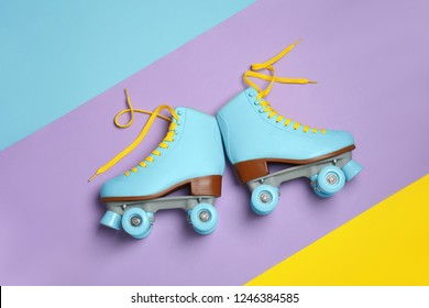 Pair of stylish quad roller skates on color background, top view