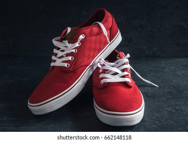 Pair of stylish red sneakers on dark background