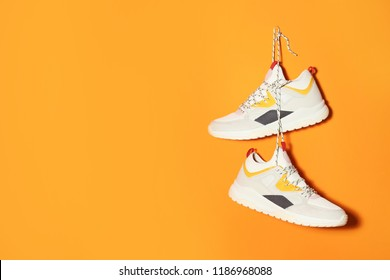 Pair of stylish sneakers hanging on color wall, space for text