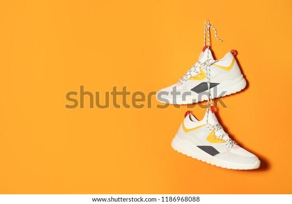 Пара стильных кроссовок висит на цветной стене, пространство для текста