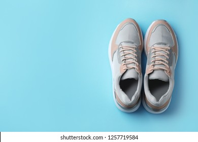 Pair of stylish sneakers on color background, top view. Space for text