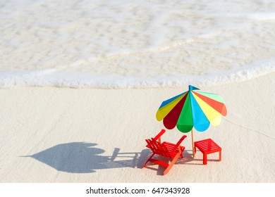 Pair of sun loungers and a beach umbrella on a deserted beach perfect vacation concept