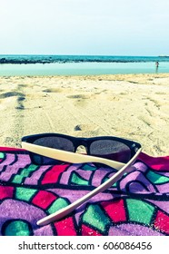 A pair of sunglasses on a colorful sarong on a sandy beach, with the blue ocean and sky in the background. Taken on Haad Khom, Ko Pha Ngan, Thailand.