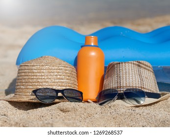 Pair of sunglasses, sunhats and sunscreen protection cream at the sand near the blue air mattress against the sea water. Illustration to a happy family summer holidays.