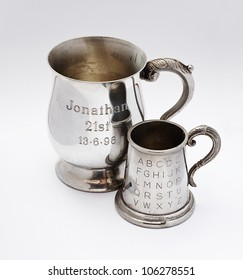 A pair of tankards with engraving celebrating anniversaries on the front