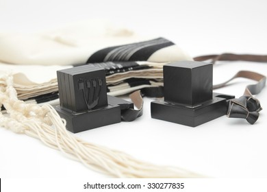 pair of tefillin and Tallit A symbol of the Jewish people, a pair of tefillin with black straps, isolated on a white background, with room for text. (Bar Mitzvah Jews 13 years old)