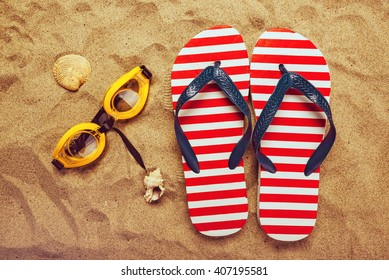 Pair of thongs or flip flops and swimming glasses on beach sand, top view of summer holiday vacation accessories