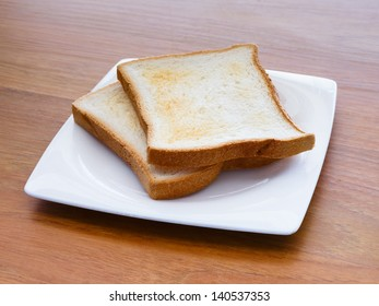A pair of toasts in a plate on a table