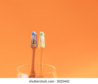 Pair of toothbrushes staring on camera.