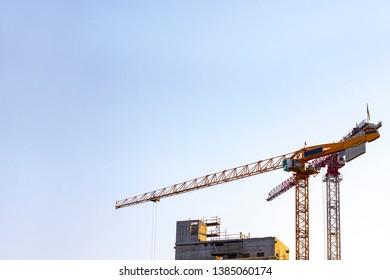 Pair of tower building cranes at the construction site in the evening sun