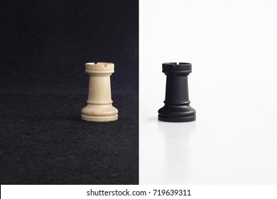 Pair of tower chess peaces confronted as opposites in black and white background.