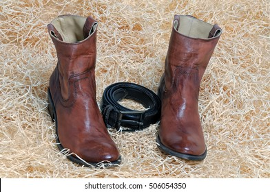 Pair of traditional brown leather cowboy boots and the leather brown belt curtailed into a ring on straw