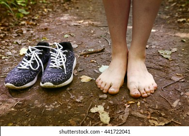 pair of trainer shoes and bare feet cose up photo on the forest path