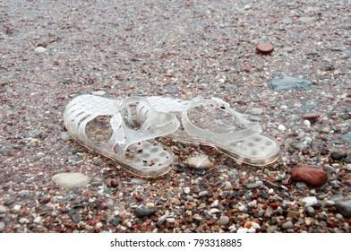 pair of transparent retro jelly sandals on sandy beach