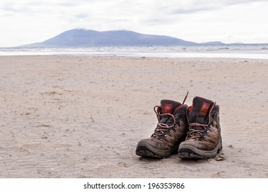 Pair of trekking shoes on a remote beach with sea and mountains in the background.