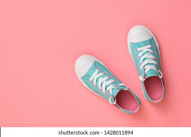 Pair of turquoise sneakers with pink insoles on pink background. Color trend 2019. Sports style. Flat lay. The view from the top.