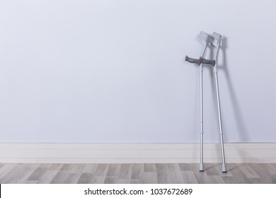 Pair Of Two Crutches Leaning On White Wall