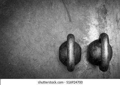 Pair of two old heavy iron kettlebells on the gym floor ready for strength and conditioning workout