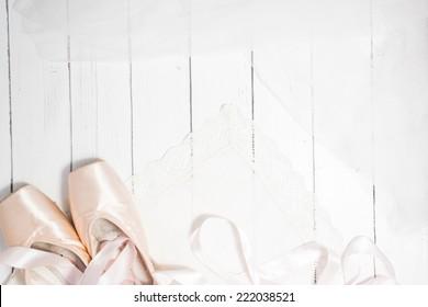 Paar aus zwei satin-russisch-rosa Ballettspitzen mit langen Bändern auf weißem Holzhintergrund.