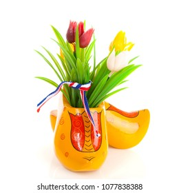 Pair of typical Dutch wooden shoes with tulips over white background