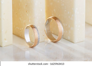 Pair of unique wedding rings with diamonds on beige background. Wedding ring bands with combined glossy and textured surface. Advertising jewelry still life