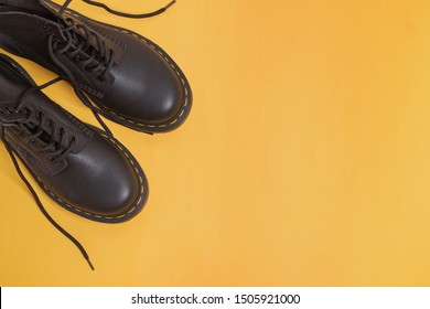Pair of unisex classic leather ankle boots on yellow background, top view