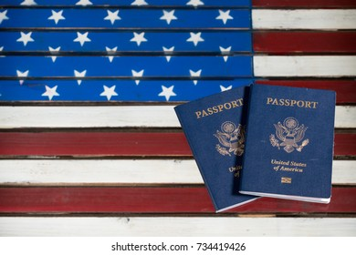 Pair of USA passports laying on a glass table over the wooden US Stars and Stripes flag
