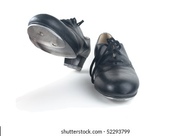 A pair of used black tap shoes with laces, one on the ground and one raised up, ready to step.  White background, shadows visible.