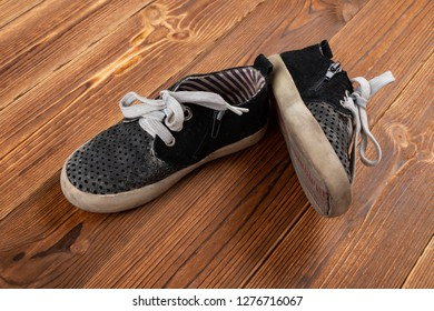 pair of used leisure shoes for kids on wood background