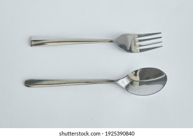 A pair of used stainless steel generic small fork and spoon. It is cutlery, tableware, kitchen supplies for all occasion. It has durable quality and timeless design.