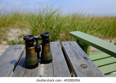 A Pair of Vintage Binoculars sitting on Wooden Table at Beach Sea Shore