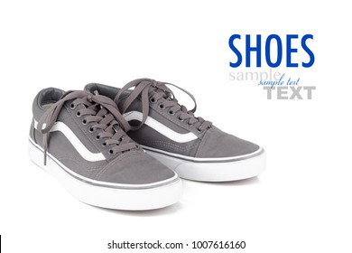 Pair of vintage grey canvas sneakers isolated on a white background with sample text. Men's old skool shoes shot in studio.